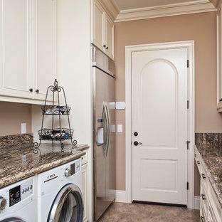 Bild på en mellanstor vintage parallell tvättstuga, med en undermonterad diskho, luckor med infälld panel, beige skåp, bänkskiva i glas, bruna väggar och en tvättmaskin och torktumlare bredvid varandra