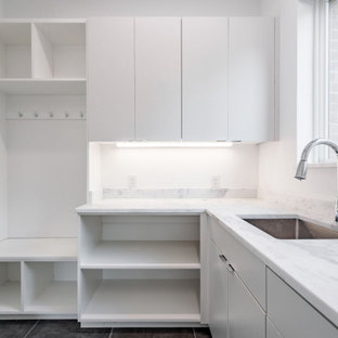 Inspiration for a large contemporary l-shaped utility room in Dallas with an utility sink, flat-panel cabinets, white cabinets, marble benchtops, white splashback, marble splashback, white walls, porcelain floors, a side-by-side washer and dryer, grey floor and yellow benchtop.