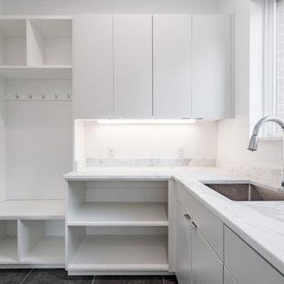 Inspiration för stora moderna l-formade gult grovkök, med en allbänk, släta luckor, vita skåp, marmorbänkskiva, vitt stänkskydd, stänkskydd i marmor, vita väggar, klinkergolv i porslin, en tvättmaskin och torktumlare bredvid varandra och grått golv