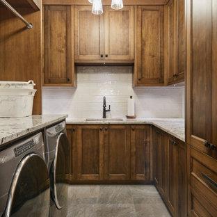 Exempel på en mellanstor rustik vita u-formad vitt tvättstuga enbart för tvätt, med en undermonterad diskho, skåp i shakerstil, skåp i mellenmörkt trä, granitbänkskiva, beige stänkskydd, stänkskydd i porslinskakel, klinkergolv i porslin, en tvättmaskin och torktumlare bredvid varandra och flerfärgat golv