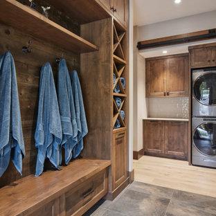 Exempel på en stor rustik liten tvättstuga, med skåp i shakerstil, skåp i mellenmörkt trä, beige stänkskydd, stänkskydd i porslinskakel, klinkergolv i porslin, en tvättpelare och flerfärgat golv