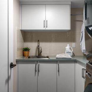 Bild på en liten blå l-formad blått tvättstuga enbart för tvätt, med en nedsänkt diskho, släta luckor, vita skåp, laminatbänkskiva, vita väggar och en tvättpelare