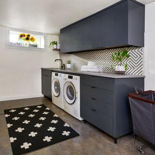 Modern inredning av en mellanstor grå linjär grått tvättstuga enbart för tvätt, med en undermonterad diskho, släta luckor, grå skåp, vita väggar, skiffergolv, en tvättmaskin och torktumlare bredvid varandra och brunt golv