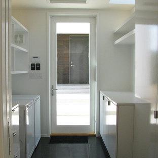Cette image montre une buanderie parallèle minimaliste dédiée et de taille moyenne avec un placard à porte plane, des portes de placard blanches, un plan de travail en surface solide, un mur blanc, des machines côte à côte, un sol en carrelage de céramique et un sol marron.