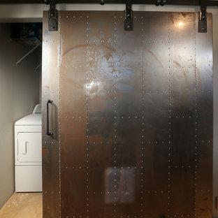 Exemple d'une grande buanderie parallèle industrielle multi-usage avec un mur gris, béton au sol et des machines côte à côte.