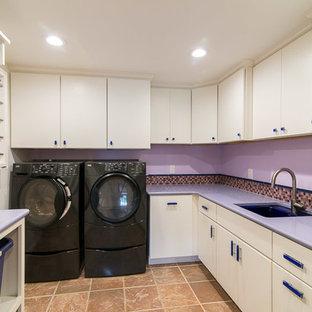 Inspiration för stora moderna parallella lila tvättstugor enbart för tvätt, med en undermonterad diskho, släta luckor, vita skåp, bänkskiva i koppar, lila väggar och en tvättmaskin och torktumlare bredvid varandra
