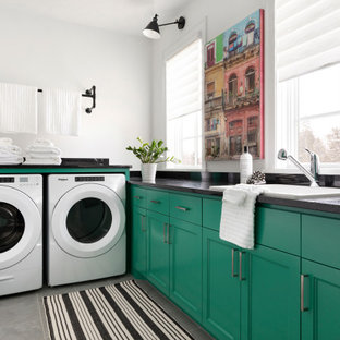 Inspiration for a medium sized contemporary l-shaped separated utility room in Minneapolis with recessed-panel cabinets, green cabinets, granite worktops, white walls, ceramic flooring, a side by side washer and dryer, grey floors, black worktops and a built-in sink.