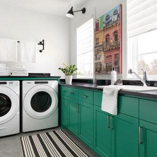 ミネアポリスの中サイズのコンテンポラリースタイルのおしゃれな洗濯室 (エプロンフロントシンク、落し込みパネル扉のキャビネット、緑のキャビネット、御影石カウンター、白い壁、セラミックタイルの床、左右配置の洗濯機・乾燥機、グレーの床、黒いキッチンカウンター) の写真