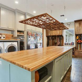 Foto på en amerikansk beige tvättstuga, med skåp i shakerstil, grå skåp, träbänkskiva, grå väggar och en tvättmaskin och torktumlare bredvid varandra