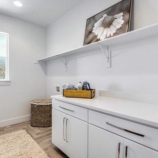 Idéer för att renovera en mellanstor vintage parallell tvättstuga enbart för tvätt, med släta luckor, vita skåp, bänkskiva i onyx, vita väggar, klinkergolv i keramik, en tvättmaskin och torktumlare bredvid varandra och brunt golv