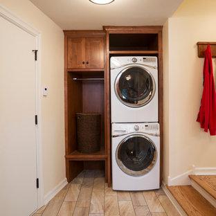 Стильный дизайн: маленькая прямая универсальная комната в классическом стиле с фасадами с утопленной филенкой, фасадами цвета дерева среднего тона, бежевыми стенами, полом из травертина и с сушильной машиной на стиральной машине - последний тренд