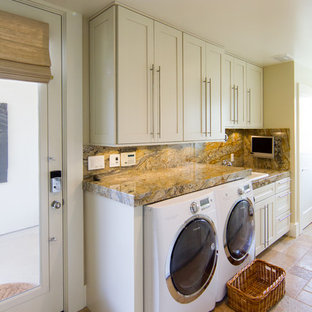 Large traditional galley separated utility room in San Luis Obispo with a single-bowl sink, raised-panel cabinets, white cabinets, granite worktops, white walls, travertine flooring and a side by side washer and dryer.