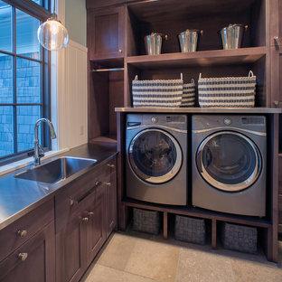 Ispirazione per una grande lavanderia classica con ante in stile shaker, ante in legno bruno, pavimento con piastrelle in ceramica, lavatrice e asciugatrice affiancate, pavimento beige, pareti verdi, top in acciaio inossidabile e top grigio