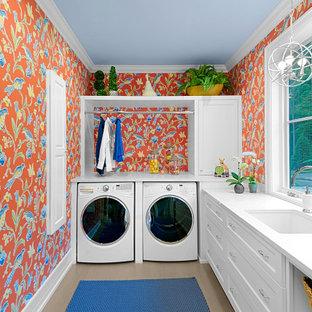 Immagine di una grande lavanderia multiuso classica con lavello sottopiano, ante in stile shaker, ante bianche, pareti multicolore, lavatrice e asciugatrice affiancate, top bianco, carta da parati, top in quarzo composito, paraspruzzi a finestra, pavimento in legno massello medio e pavimento marrone