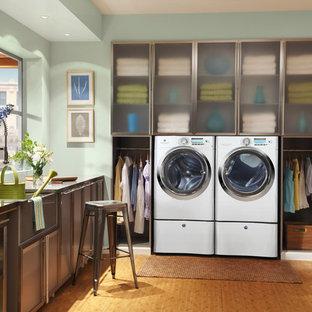 Exempel på ett mellanstort klassiskt l-format grovkök, med en rustik diskho, luckor med glaspanel, skåp i rostfritt stål, bänkskiva i rostfritt stål, gröna väggar, mellanmörkt trägolv och en tvättmaskin och torktumlare bredvid varandra