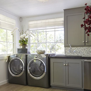 Design ideas for a large contemporary single-wall utility room in Miami with a submerged sink, shaker cabinets, engineered stone countertops, medium hardwood flooring, a side by side washer and dryer, grey cabinets and white walls.