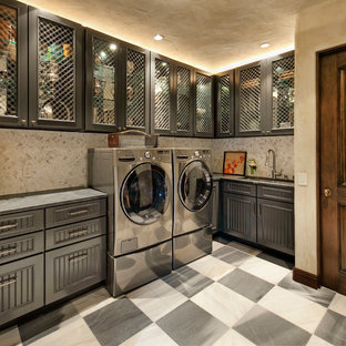 Inredning av en medelhavsstil stor l-formad tvättstuga enbart för tvätt, med en undermonterad diskho, luckor med glaspanel, grå skåp, marmorbänkskiva, beige väggar, klinkergolv i porslin och en tvättmaskin och torktumlare bredvid varandra