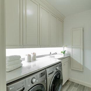 Foto på en liten vintage grå linjär tvättstuga enbart för tvätt, med en nedsänkt diskho, luckor med profilerade fronter, vita skåp, bänkskiva i kvartsit, vita väggar, en tvättmaskin och torktumlare bredvid varandra och grått golv
