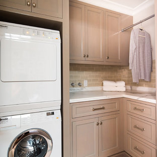 Example of a small classic l-shaped laundry room design in Los Angeles with recessed-panel cabinets, light wood cabinets, white walls, a stacked washer/dryer and white countertops