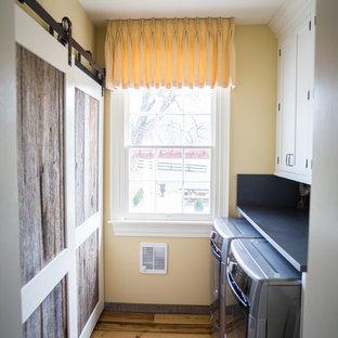 Idee per una sala lavanderia country di medie dimensioni con ante in stile shaker, ante bianche, pareti gialle, parquet chiaro, lavatrice e asciugatrice affiancate, pavimento marrone e top in cemento