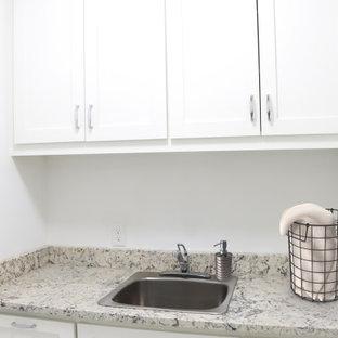 Modern inredning av en beige beige tvättstuga enbart för tvätt, med en nedsänkt diskho, skåp i shakerstil, vita skåp, granitbänkskiva, vita väggar, klinkergolv i porslin, en tvättmaskin och torktumlare bredvid varandra och vitt golv