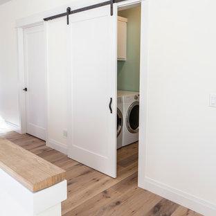 Cette image montre une buanderie linéaire minimaliste de taille moyenne avec un placard, un placard à porte shaker, des portes de placard blanches, un mur vert, un sol en bois clair et des machines côte à côte.