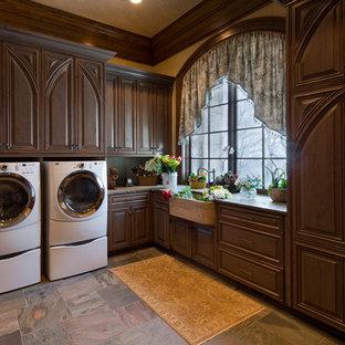 Idee per un'ampia sala lavanderia vittoriana con ante con bugna sagomata, lavello stile country, ante in legno bruno e top in granito