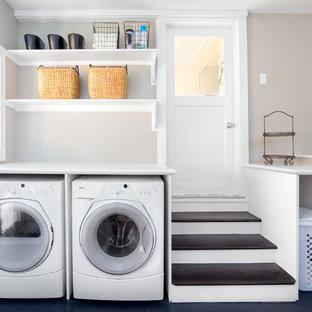 Exempel på en stor klassisk vita vitt tvättstuga enbart för tvätt, med vita skåp, laminatbänkskiva, betonggolv, en tvättmaskin och torktumlare bredvid varandra, öppna hyllor, svart golv och grå väggar