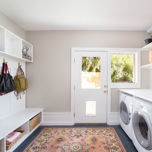 Inspiration for a large contemporary single-wall utility room in Boise with white cabinets, laminate countertops, concrete flooring, a side by side washer and dryer, black floors and grey walls.
