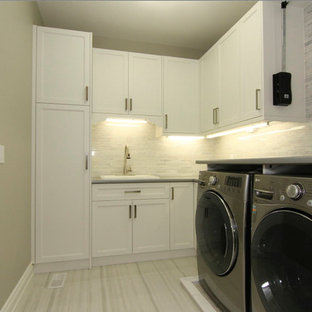 Inspiration for a large classic galley separated utility room in Toronto with a single-bowl sink, recessed-panel cabinets, white cabinets, laminate countertops, carpet, a side by side washer and dryer and grey walls.