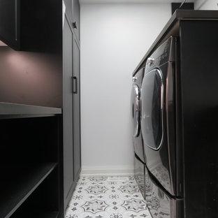 Foto di una sala lavanderia minimalista di medie dimensioni con lavello da incasso, ante lisce, ante nere, top in granito, pareti bianche, pavimento con piastrelle in ceramica, lavatrice e asciugatrice affiancate, pavimento multicolore e top nero