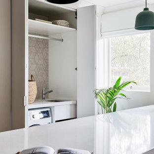 Idéer för att renovera en liten funkis vita linjär vitt liten tvättstuga, med en undermonterad diskho, vita skåp, bänkskiva i kvarts, vita väggar, ljust trägolv, en tvättmaskin och torktumlare bredvid varandra och brunt golv