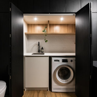 Inspiration for a large contemporary galley utility room in Melbourne with porcelain flooring, brown floors, a built-in sink, open cabinets, light wood cabinets, laminate countertops, white walls, an integrated washer and dryer and white worktops.