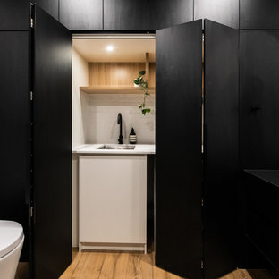 Design ideas for a large contemporary galley utility room in Melbourne with porcelain flooring, brown floors, a built-in sink, open cabinets, light wood cabinets, laminate countertops, white walls, an integrated washer and dryer and white worktops.