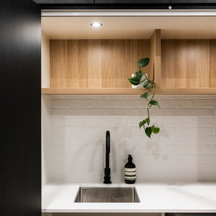 Large contemporary galley utility room in Melbourne with porcelain flooring, brown floors, a built-in sink, open cabinets, light wood cabinets, laminate countertops, white walls, an integrated washer and dryer and white worktops.