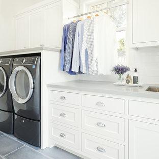 Lantlig inredning av en grå linjär grått tvättstuga enbart för tvätt, med en undermonterad diskho, skåp i shakerstil, vita skåp, bänkskiva i kvarts, vita väggar, klinkergolv i porslin, en tvättmaskin och torktumlare bredvid varandra och grått golv