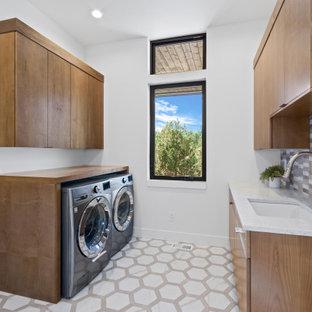 Idéer för att renovera en stor funkis vita parallell vitt tvättstuga enbart för tvätt, med en undermonterad diskho, släta luckor, skåp i mellenmörkt trä, bänkskiva i kvarts, flerfärgad stänkskydd, stänkskydd i stenkakel, vita väggar, klinkergolv i keramik, en tvättmaskin och torktumlare bredvid varandra och vitt golv