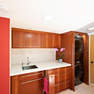 Идея дизайна: маленькая прямая универсальная комната в стиле модернизм с врезной раковиной, плоскими фасадами, фасадами цвета дерева среднего тона, столешницей из кварцевого агломерата, красными стенами, светлым паркетным полом, со скрытой стиральной машиной, коричневым полом и белой столешницей