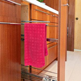 Foto di una piccola lavanderia multiuso minimalista con lavello sottopiano, ante lisce, ante in legno scuro, top in quarzo composito, pareti rosse, parquet chiaro, lavatrice e asciugatrice nascoste, pavimento marrone e top bianco