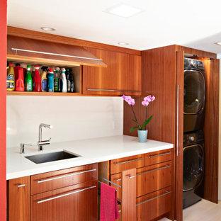 Foto på ett litet funkis vit linjärt grovkök, med en undermonterad diskho, släta luckor, skåp i mellenmörkt trä, bänkskiva i kvarts, röda väggar, ljust trägolv, tvättmaskin och torktumlare byggt in i ett skåp och brunt golv
