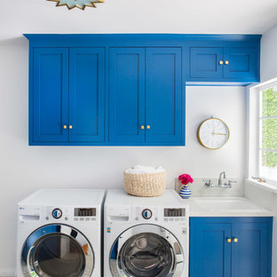 Photo of a traditional single-wall separated utility room in Los Angeles with a submerged sink, shaker cabinets, blue cabinets, grey walls, a side by side washer and dryer and grey floors.