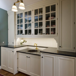 Design ideas for a small traditional single-wall utility room in Chicago with a single-bowl sink, beaded cabinets, white cabinets, soapstone worktops, green walls, medium hardwood flooring, a concealed washer and dryer and black worktops.