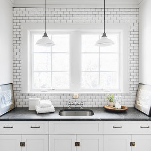This is an example of a small classic single-wall utility room in Chicago with a submerged sink, shaker cabinets, grey cabinets, granite worktops, white walls, a stacked washer and dryer, multi-coloured floors, black worktops and concrete flooring.
