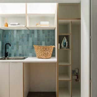 Idéer för att renovera en retro vita vitt tvättstuga, med en enkel diskho, vita skåp, laminatbänkskiva, blått stänkskydd, stänkskydd i tunnelbanekakel, blå väggar, klinkergolv i porslin och grått golv