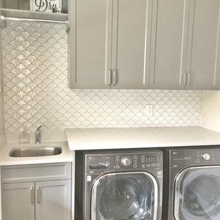Lantlig inredning av en vita linjär vitt tvättstuga enbart för tvätt, med en undermonterad diskho, släta luckor, grå skåp, bänkskiva i kvarts, vita väggar, vinylgolv, en tvättmaskin och torktumlare bredvid varandra och flerfärgat golv
