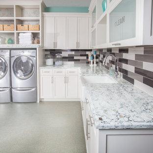 Immagine di una grande lavanderia classica con lavello stile country, ante in stile shaker, ante bianche, top in quarzo composito, pareti blu, pavimento in laminato e lavatrice e asciugatrice affiancate