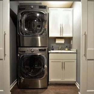 Inredning av en klassisk liten linjär liten tvättstuga, med en enkel diskho, vita skåp, grå väggar, mellanmörkt trägolv, en tvättpelare, brunt golv och skåp i shakerstil