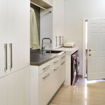 Trendy limestone floor and beige floor laundry room photo in Toronto with stainless steel countertops, a side-by-side washer/dryer, white cabinets, an integrated sink and white walls