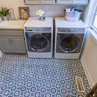 Inspiration for a large contemporary concrete floor and blue floor dedicated laundry room remodel in Minneapolis with a drop-in sink, raised-panel cabinets and gray walls