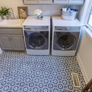Idee per una grande sala lavanderia contemporanea con pavimento in cemento, lavatrice e asciugatrice affiancate, pavimento blu, lavello da incasso, ante con bugna sagomata e pareti grigie